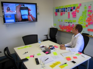 A note taker observing the video feed from the next room, taking notes on post-its.